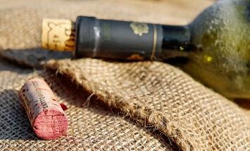 bottiglia di vino coricata e alcuni tappi su sacco di iuta
