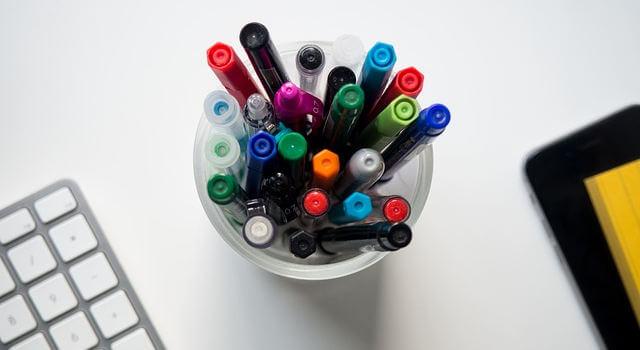 scrivania con penne e tastiera